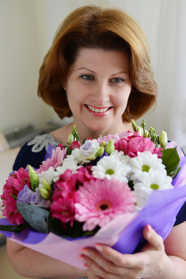 Positive Woman with a bouquet of flowers in the room royalty free stock image