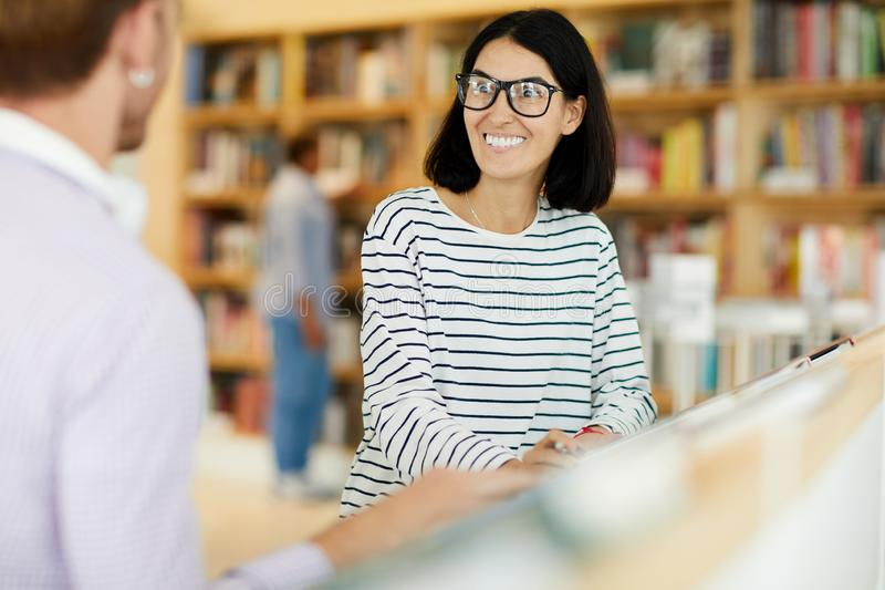 Positive woman chatting with friend in bookstore. Positive excited young women in glasses having crazy smile while chatting with friend in bookstore stock photo