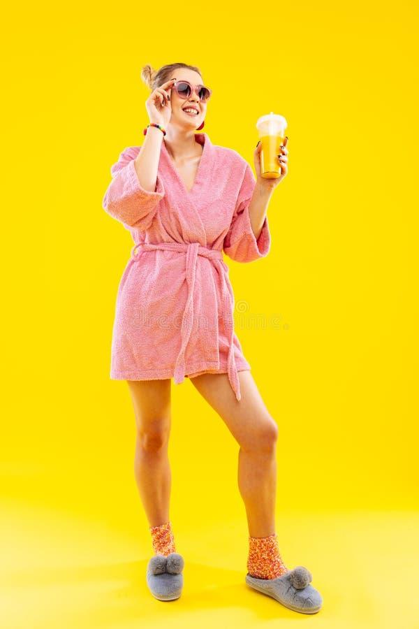 Cheerful positive woman wearing pink bathrobe drinking juice. Positive woman. Cheerful positive blonde-haired woman wearing pink bathrobe drinking juice royalty free stock image