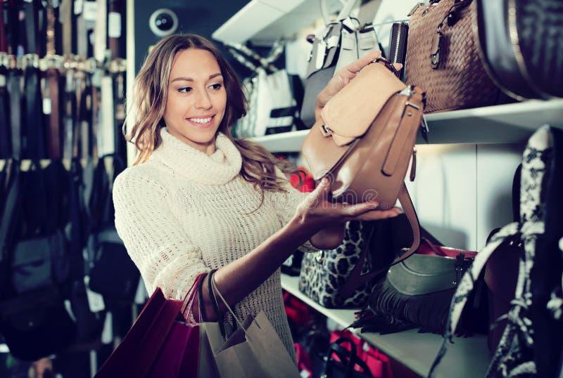 Download Positive Woman Choosing Bag Among Assortment Stock Photo - Image: 83703158
