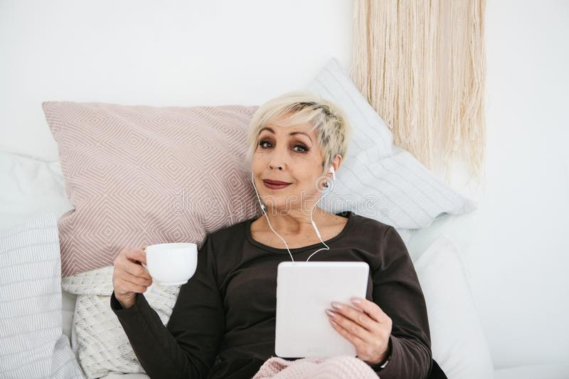 A positive woman drinks a morning coffee lying in bed and uses a tablet to watch videos, listen to music and chat with. Friends on social networks royalty free stock images