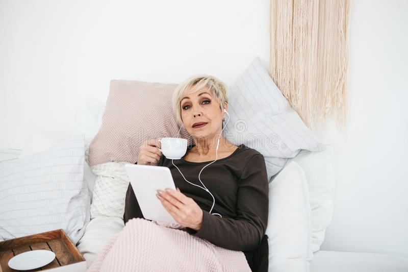 A positive woman drinks a morning coffee lying in bed and uses a tablet to watch videos, listen to music and chat with royalty free stock photos