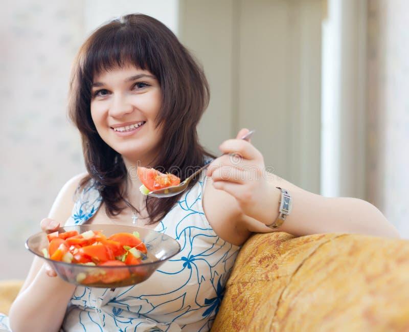 Positive  Woman Eats Veggie Salad On Sofa Royalty Free Stock Image