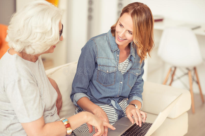 Positive woman and her senior mother using laptop. Show me how it works. Cheerful smiling beautiful women sitting on the couch with her aged mother and showing stock photography