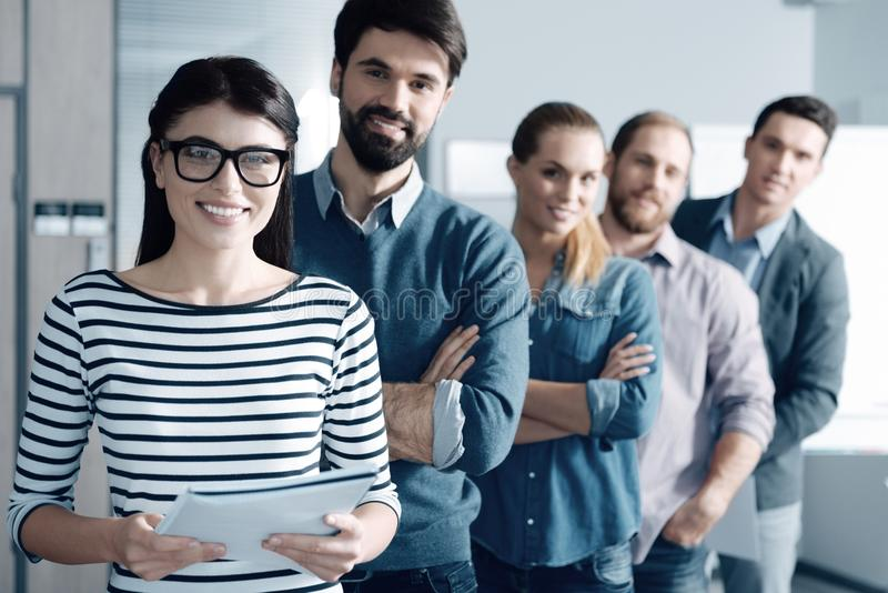 Positive woman and her team standing in the office stock photography