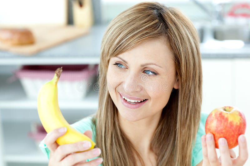 Download Positive Woman Holding A Banana And An Apple Stock Image - Image: 15615589