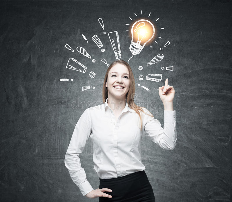 Positive woman, light bulb and exclamations. Portrait of a positive blond woman standing near a blackboard with a light bulb drawing surrounded by exclamation stock photography