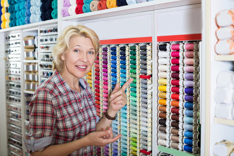 Positive woman picking stitching spools stock photos