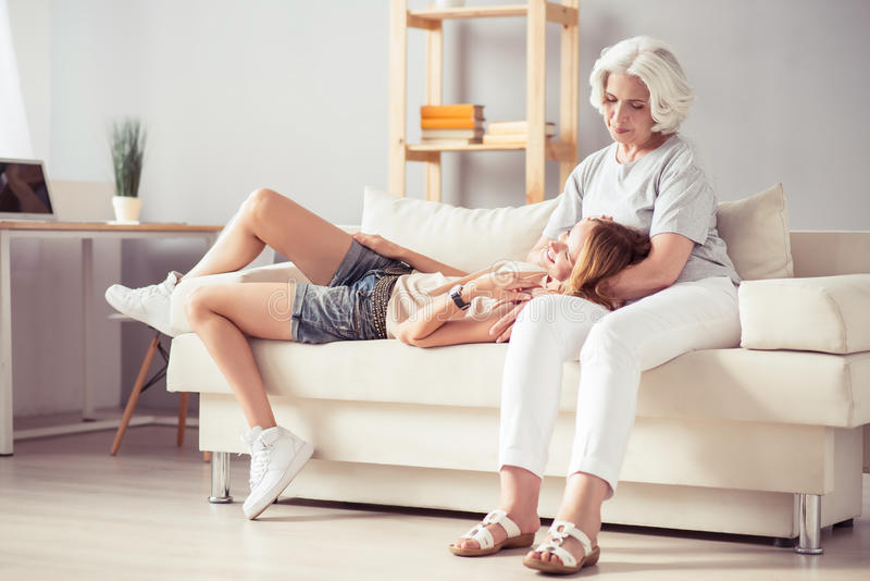 Positive woman resting on the couch with her aged mother stock photography
