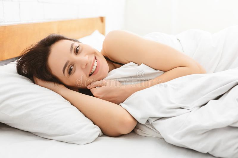 Positive woman smiling at camera, lying in bed after good sleep royalty free stock image