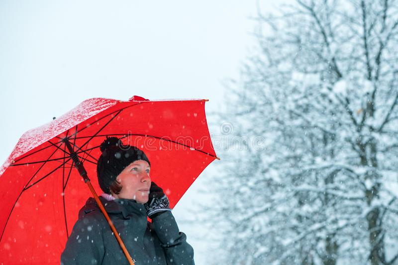 Positive woman talking on mobile phone under umbrella in snow stock photos