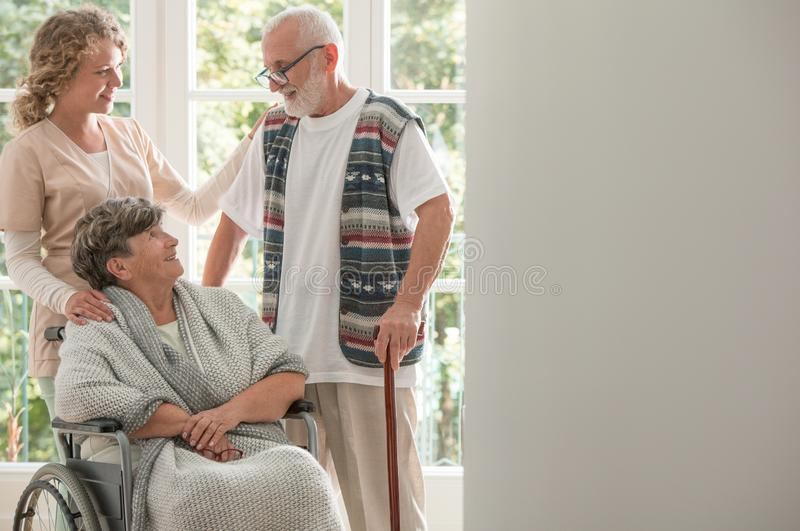 Positive woman on wheelchair with caring nurse and elderly friend with walking stick royalty free stock photos