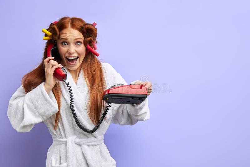Positive woman in white bathrobe talking on landline phone royalty free stock images