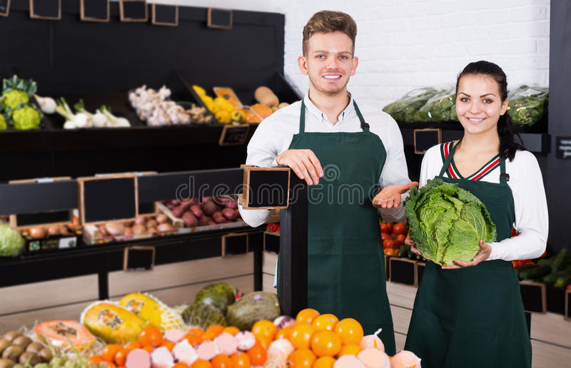 Positive young assistants displaying assortment stock image