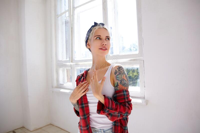 Positive young attractive blonde woman with tattoos dressed in checkered shirt keeping palms on chest while looking gladly aside,. Posing in front of big window stock image