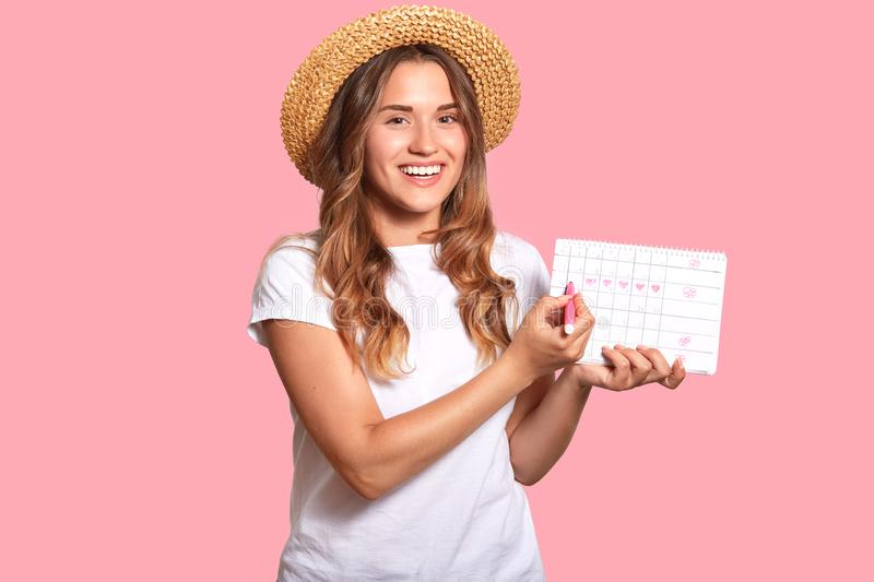 Positive young Caucasian woman with wavy hair, dressed in casual white t shirt, headgear holds period calendar, shows day of. Ovulation, plans pregnancy royalty free stock image
