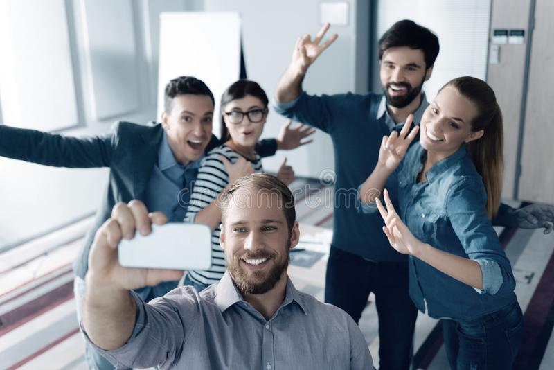 Positive young colleagues making selfies royalty free stock images