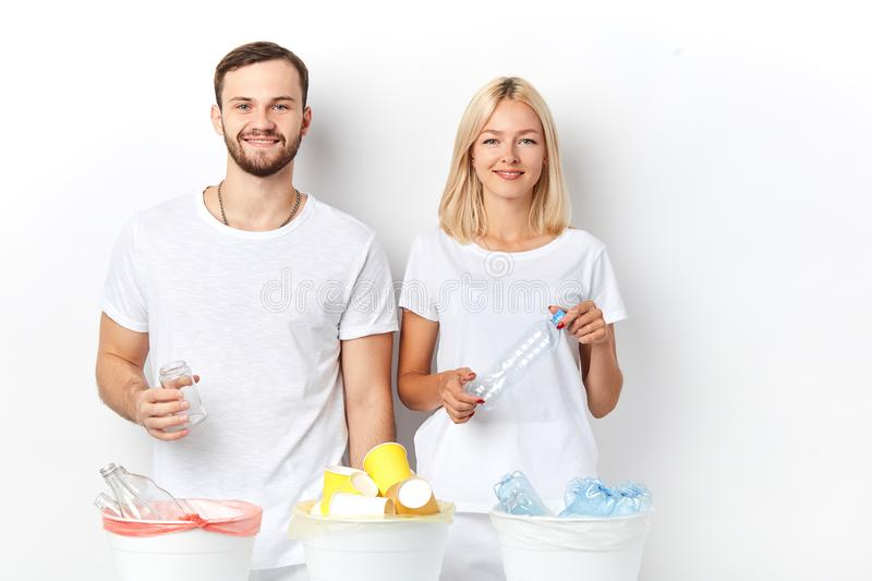 Positive young couple doing their bit to save the environment. Thoughtful consumer. close up portrait, studio shot royalty free stock photography