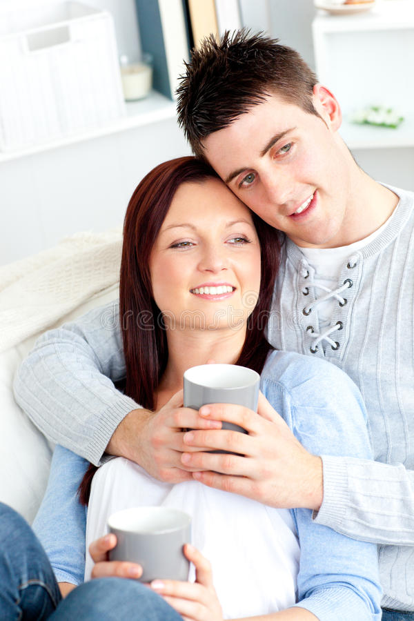 Positive Young Couple Drinking Coffee On A Sofa Stock Photo