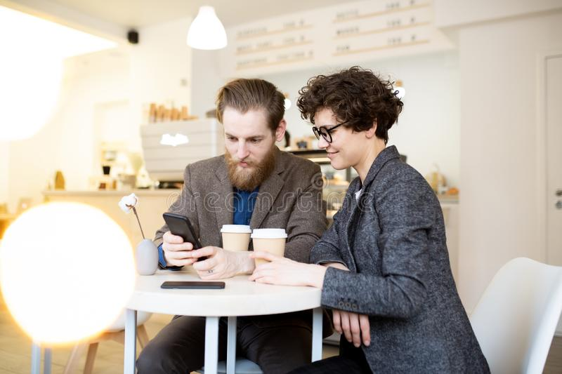 Positive couple viewing online source on phone stock images