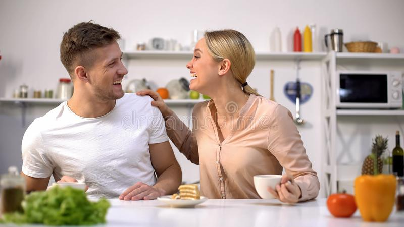 Positive young couple laughing as having breakfast, fooling around together stock images
