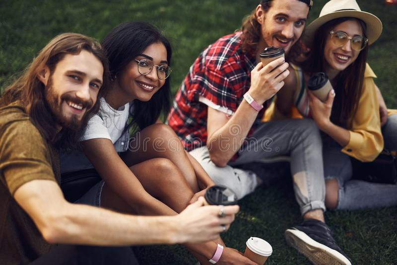Two couples smiling and looking at you while sitting on the grass stock photos