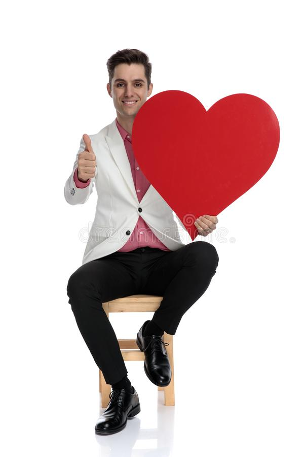 Positive young elegant man makes ok sign while holding heart royalty free stock image
