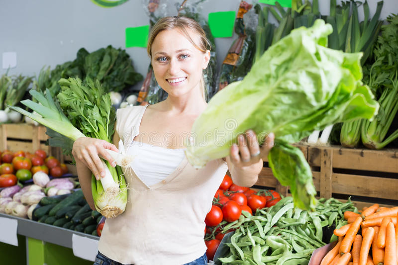 Positive young female customer holding fresh celery and leek stock image