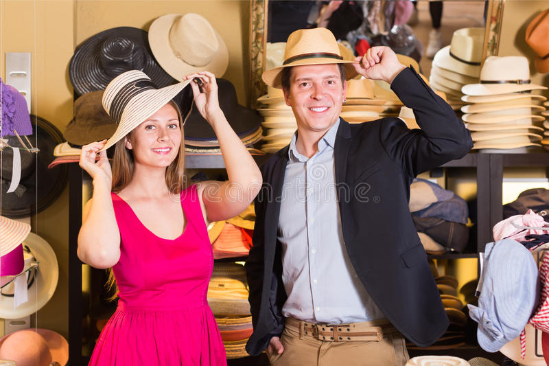 Positive young female and man choosing hats in the store royalty free stock images