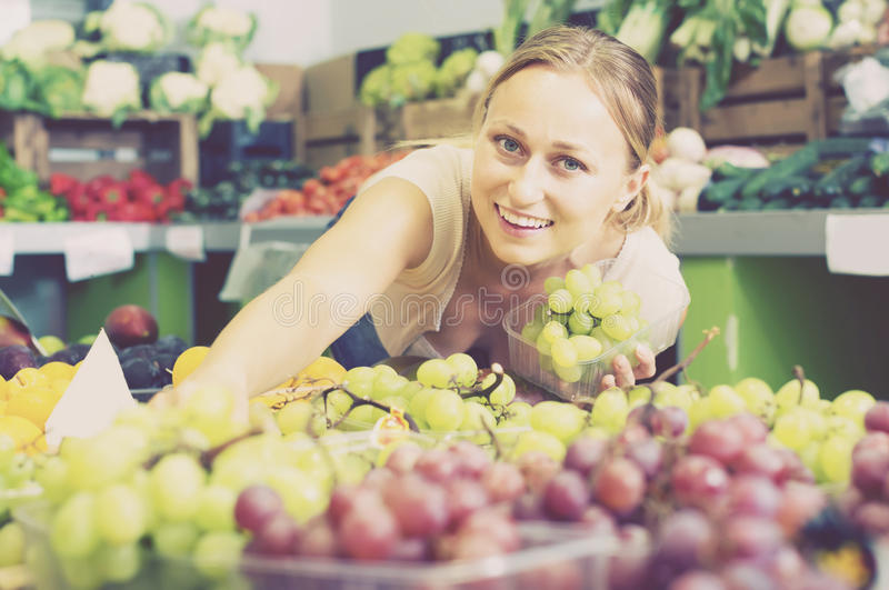Positive young female seller holding bunch of grapes on market stock photo
