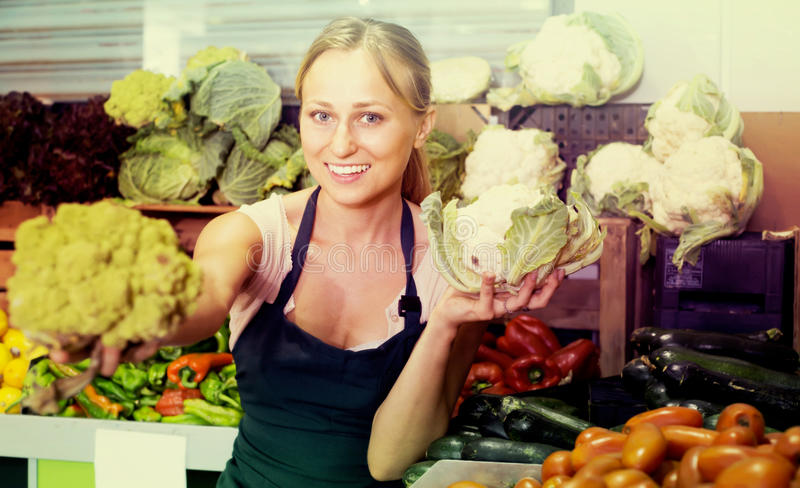 Positive young female seller holding fresh cabbage on market royalty free stock photo