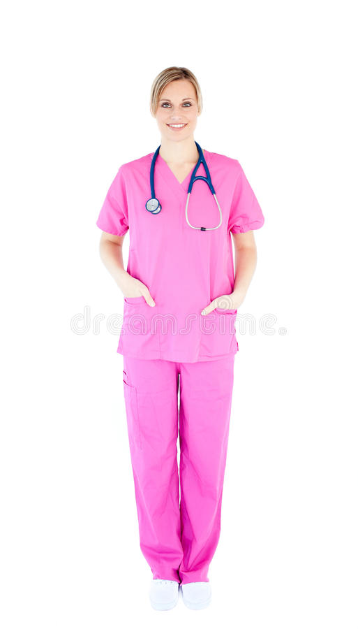 Positive young female surgeon wearing scrubs. Against white background royalty free stock photo