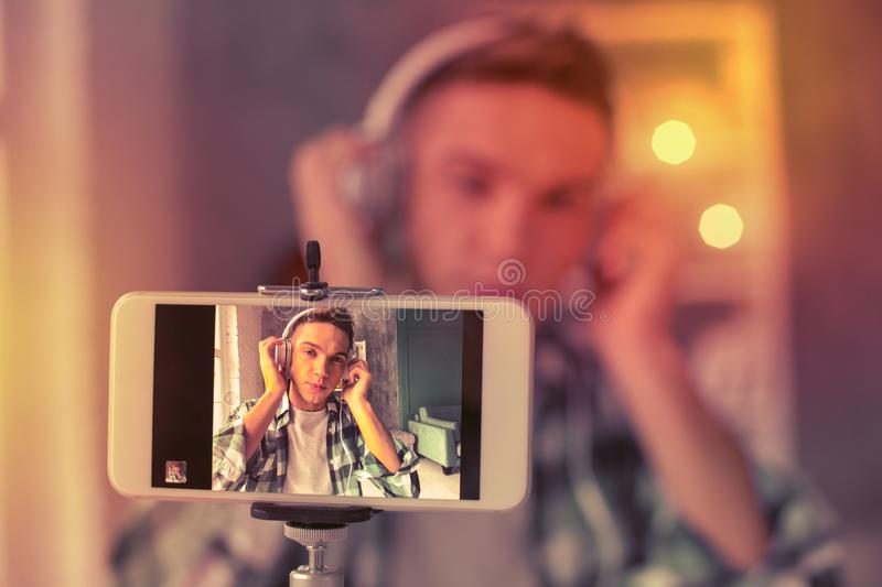 Positive young guy creating music video content royalty free stock photography