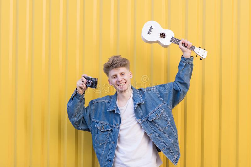Positive young hipsters with ukulele and camera in their hands poses against the background of the yellow wall royalty free stock photo
