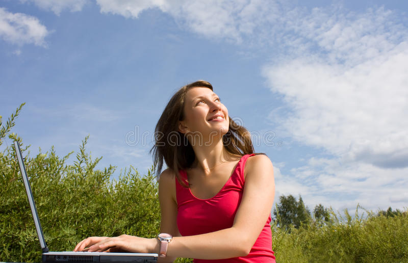 Positive young lady is looking up. Laptop stock image