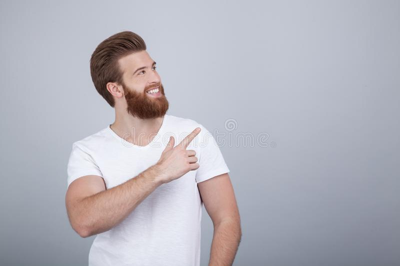 Positive young male freelancer or blogger being satisfied with results of work, has friendly pleasant smile, points upwards with royalty free stock image
