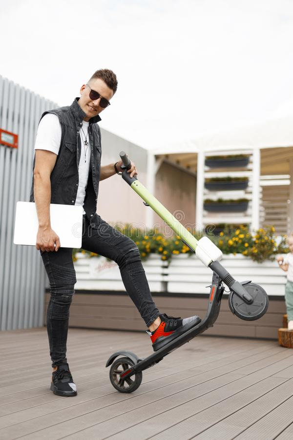 Positive young man hipster in sunglasses in stylish black clothes with a modern laptop poses on a electric scooter. Joyful guy. Freelancer with a cute smile on royalty free stock image