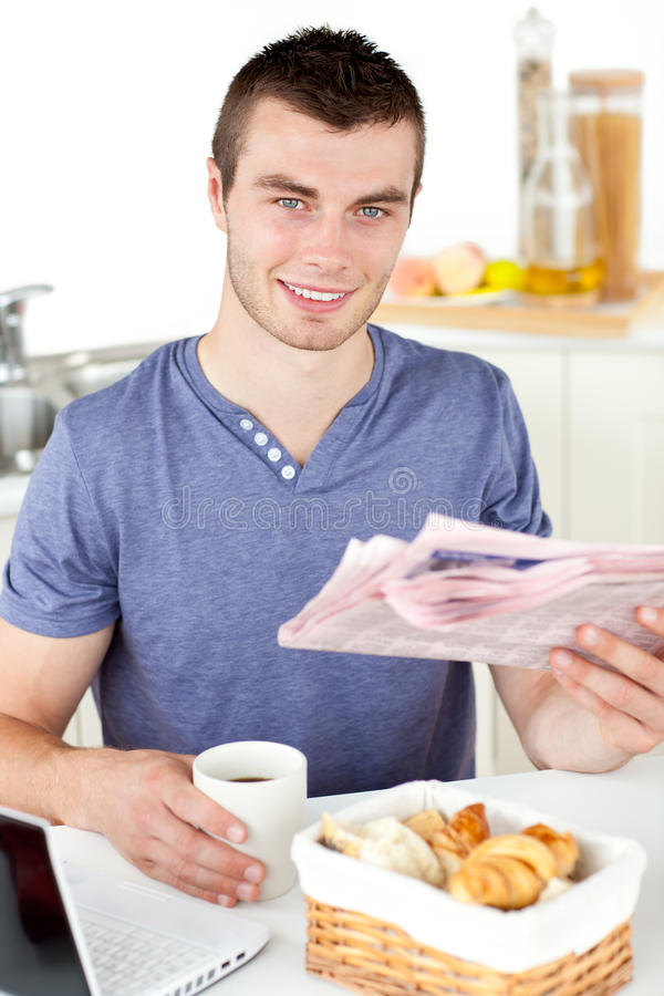 Download Positive Young Man Holding A Cup And A Newspaper Stock Photo - Image: 15786624