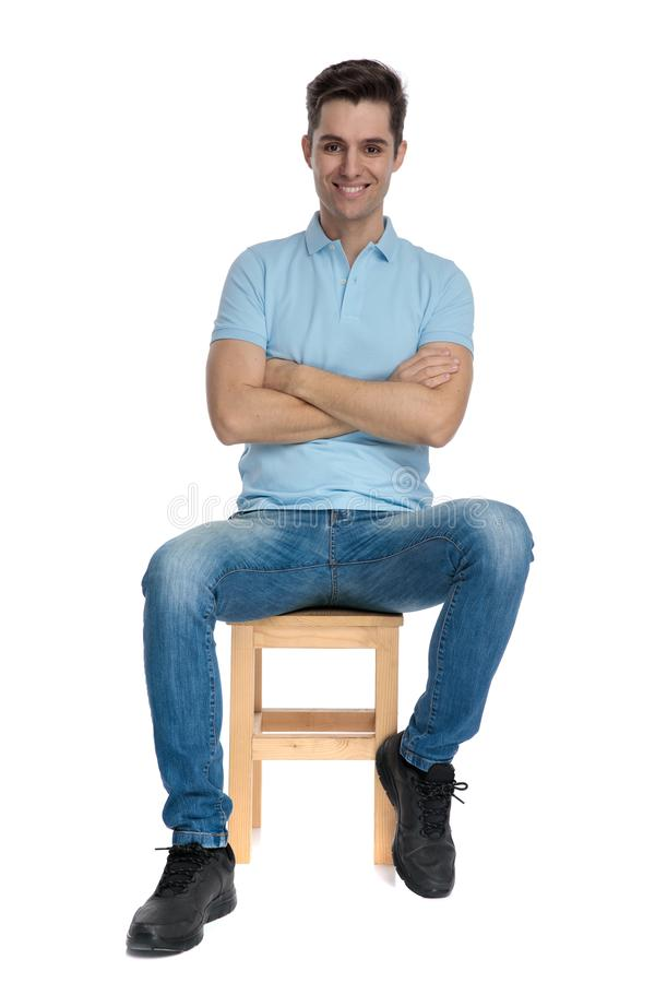 Positive young man sitting with his arms folded and smiling. While wearing a blue shirt on white studio background royalty free stock photo