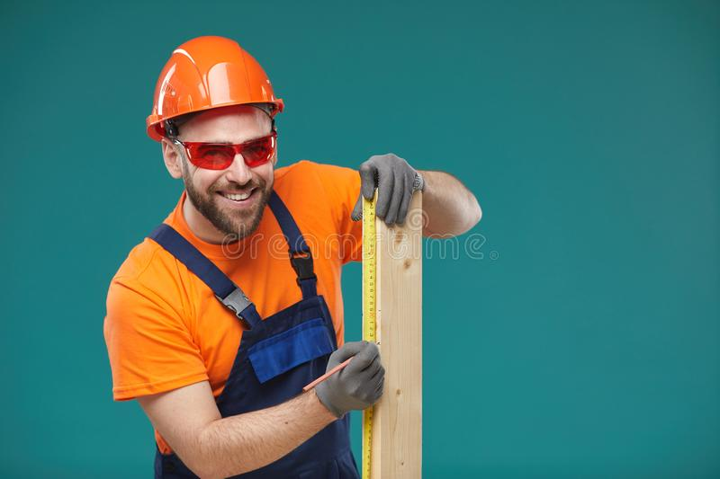 Positive Young Man Sizing Wooden Plank royalty free stock photography