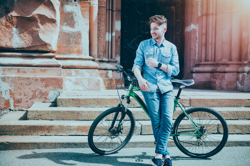 Positive young man standing near his bicycle royalty free stock images