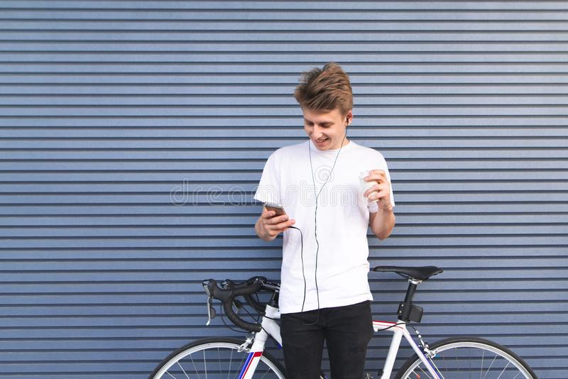 Positive young man stands beside a bicycle against the wall, looks at the smartphone and smiles stock images