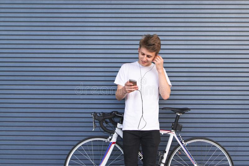 Positive young man stands by a white bicycle, listens to music in the headphones and looks at the smartphone royalty free stock images