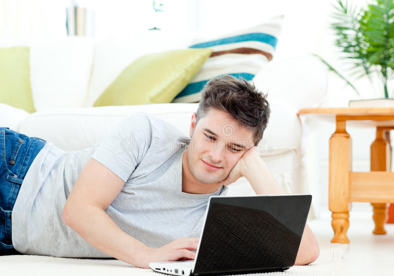 Download Positive Young Man Using His Laptop On The Floor Stock Photo - Image of notebook, male: 15518112