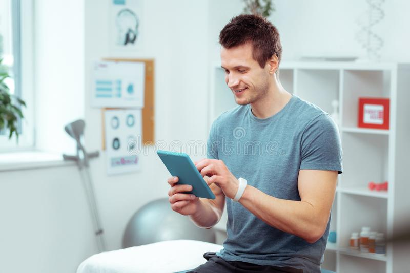 Positive young man waiting for his doctor stock photography
