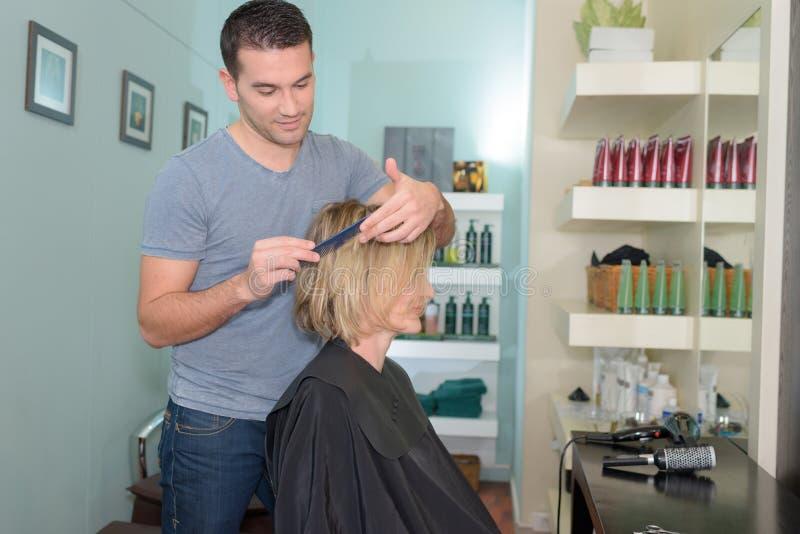 Positive young man cutting hair girl in hairdressing salon stock photos