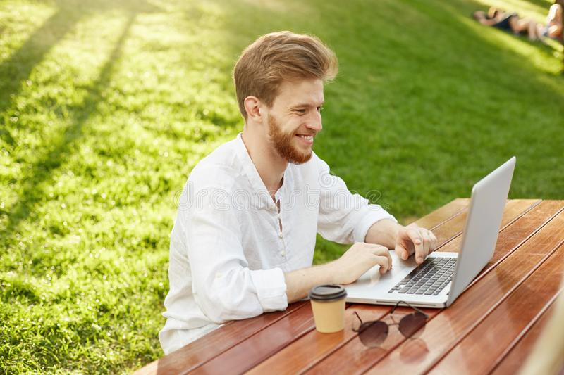 Positive young red-haired unshaven guy in white shirt smiling, sitting in beautiful park, drinking coffee and writing stock images