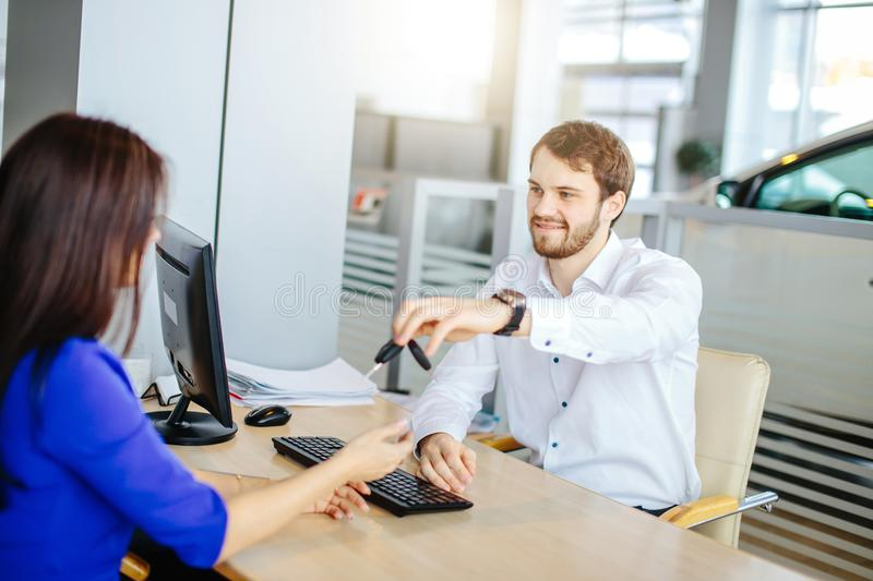 Positive young seller man handing over car key to ner owner royalty free stock photography