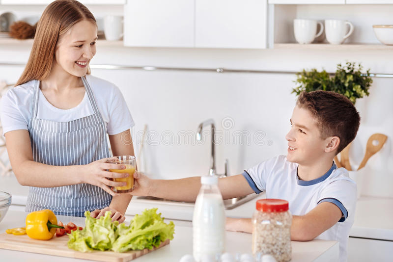 Positive young siblings standing in the kitchen stock image