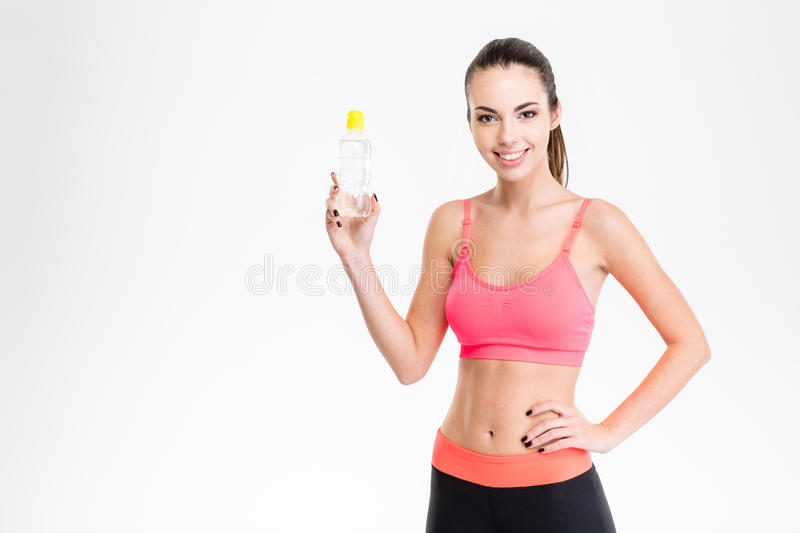 Positive young sportswoman holding a bottle of water. Isolated over white background stock photos